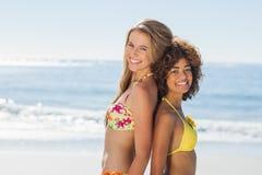 Amis de sourire dans des bikinis se tenant de nouveau au dos Photo libre de droits
