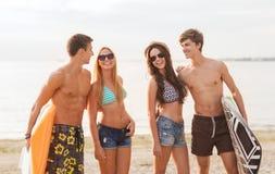Amis de sourire dans des lunettes de soleil avec des ressacs sur la plage Photos stock