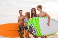 Amis de sourire dans des lunettes de soleil avec des ressacs sur la plage Images stock