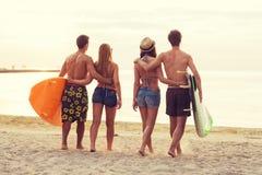 Amis de sourire dans des lunettes de soleil avec des ressacs sur la plage Photographie stock libre de droits