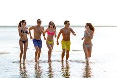 Amis de sourire dans des lunettes de soleil fonctionnant sur la plage Photos libres de droits