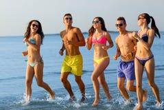 Amis de sourire dans des lunettes de soleil fonctionnant sur la plage Photo stock