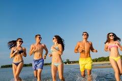 Amis de sourire dans des lunettes de soleil fonctionnant sur la plage Photographie stock libre de droits