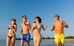 Amis de sourire dans des lunettes de soleil fonctionnant sur la plage Photo libre de droits