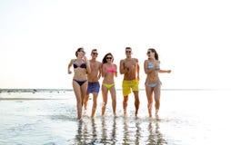 Amis de sourire dans des lunettes de soleil fonctionnant sur la plage Photos stock