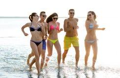 Amis de sourire dans des lunettes de soleil fonctionnant sur la plage Photographie stock