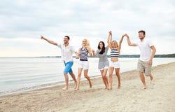 Amis de sourire dans des lunettes de soleil fonctionnant sur la plage Images libres de droits