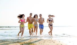 Amis de sourire dans des lunettes de soleil fonctionnant sur la plage Image stock