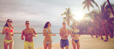 Amis de sourire dans des lunettes de soleil fonctionnant sur la plage Image libre de droits