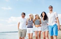 Amis de sourire dans des lunettes de soleil marchant sur la plage Photos libres de droits