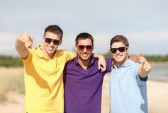 Amis de sourire dans des lunettes de soleil montrant des pouces  Image stock