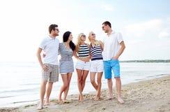 Amis de sourire dans des lunettes de soleil parlant sur la plage Photos stock