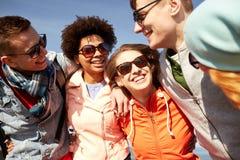Amis de sourire dans des lunettes de soleil riant sur la rue Photographie stock libre de droits