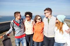 Amis de sourire dans des lunettes de soleil riant sur la rue Photos stock