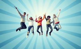 Amis de sourire dans des lunettes de soleil sautant haut Photo stock