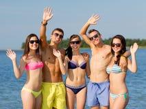 Amis de sourire dans des lunettes de soleil sur la plage d'été Photos stock