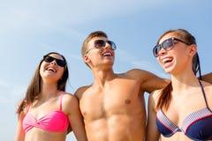 Amis de sourire dans des lunettes de soleil sur la plage d'été Photographie stock