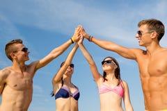 Amis de sourire dans des lunettes de soleil sur la plage d'été Photo stock