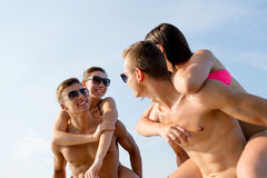 Amis de sourire dans des lunettes de soleil sur la plage d'été Photographie stock libre de droits