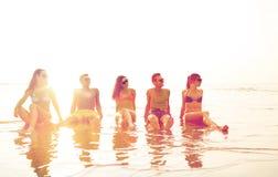 Amis de sourire dans des lunettes de soleil sur la plage d'été Images libres de droits