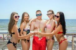 Amis de sourire dans des maillots de bain sur un fond bleu de mer Un portrait d'été des personnes heureuses Amis détendant sur a Photo libre de droits
