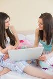 Amis de sourire dans des pyjamas parlant sur le lit utilisant un ordinateur portable Photo stock