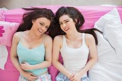 Amis de sourire dans des pyjamas regardant l'appareil-photo sur le lit Photo stock