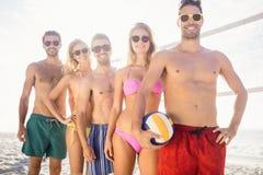 Amis de sourire dans la ligne après avoir joué le volleyball Image libre de droits