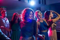Amis de sourire dansant dans le club Image stock