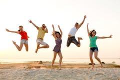 Amis de sourire dansant et sautant sur la plage Images libres de droits