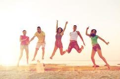 Amis de sourire dansant et sautant sur la plage Photo stock