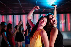 Amis de sourire dansant sur la piste de danse Photo stock