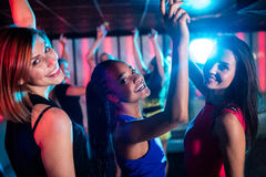 Amis de sourire dansant sur la piste de danse Images stock