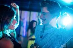 Amis de sourire dansant sur la piste de danse Photos stock
