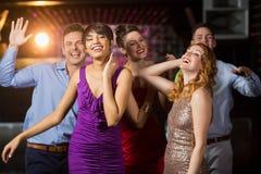 Amis de sourire dansant sur la piste de danse Photographie stock libre de droits
