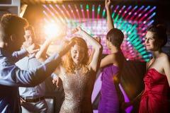 Amis de sourire dansant sur la piste de danse Image stock