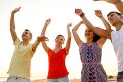 Amis de sourire dansant sur la plage d'été Photo stock