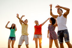 Amis de sourire dansant sur la plage d'été Image stock