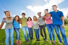 Amis de sourire de diversité se tenant sur l'herbe dans la rangée Photographie stock libre de droits