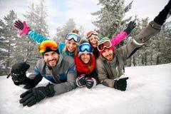 Amis de sourire des vacances d'hiver - skieurs se trouvant sur la neige et l'ha Images libres de droits