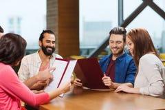 Amis de sourire discutant le menu au restaurant Image libre de droits