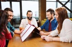 Amis de sourire discutant le menu au restaurant Photographie stock
