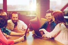 Amis de sourire discutant le menu au restaurant Images stock