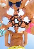 Amis de sourire en cercle sur la plage d'été Photographie stock