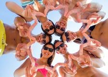 Amis de sourire en cercle sur la plage d'été Image libre de droits
