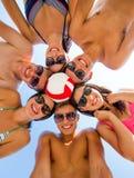 Amis de sourire en cercle sur la plage d'été Photo libre de droits