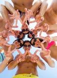 Amis de sourire en cercle sur la plage d'été Photo stock