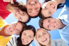 Amis de sourire en cercle sur la plage d'été Photographie stock libre de droits