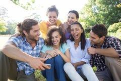 Amis de sourire en parc prenant le selfie Photographie stock libre de droits