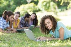 Amis de sourire en parc utilisant le PC et l'ordinateur portable de comprimé Photo libre de droits